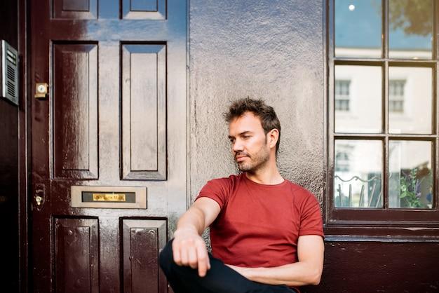 Mann, der in einer bank auf einem schönen kastanienbraunen hintergrund sitzt