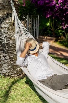 Mann, der in einer hängematte im garten sich entspannt.