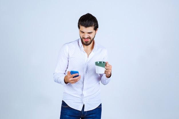 Mann, der in einer hand eine kaffeetasse hält und in der anderen auf sein telefon schaut