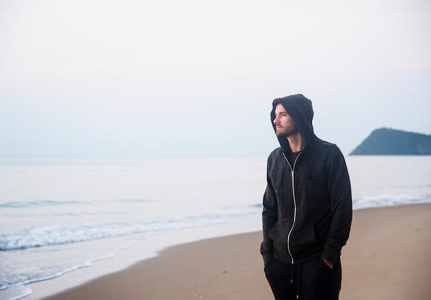 Mann, der in einsamkeit am strand geht