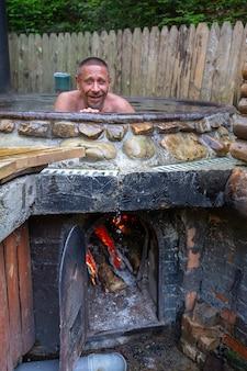 Mann, der in gusseisernem bottich mit schwefelwasserstoff enthaltendem mineralwasser badet