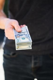 Mann, der in händen dollar hält