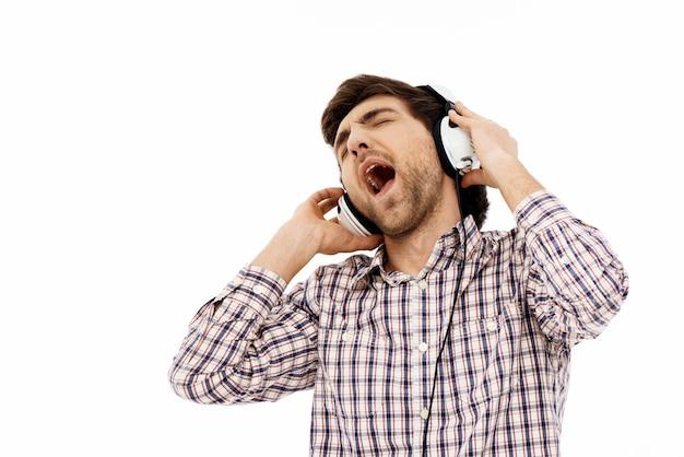 Mann, der in kopfhörern singt, genießt, musik zu hören