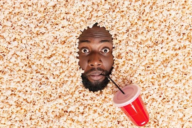 Mann, der in popcorn ertrunken ist, trinkt limonade, sieht film im kino überrascht aus angst vor horrorszene im film sieht aufgeregt aus