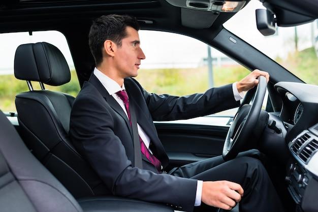 Mann, der in sein auto in der geschäftskleidung fährt