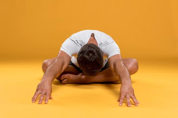 Mann, der in yogahaltung ausdehnt