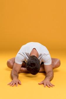 Mann, der in yogastellung meditiert