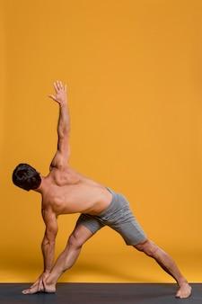 Mann, der in yogastellung übt