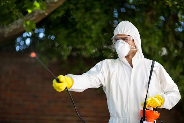 Mann, der insektizid bei der stellung gegen baum verwendet