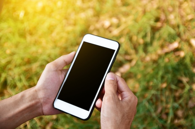 Mann, der intelligentes mobiltelefon unter verwendung der intelligenten anwendung durch internet online hält