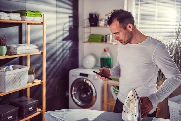 Mann, der intelligentes telefon beim bügeln von kleidung verwendet