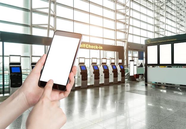 Mann, der intelligentes telefonmobile im flughafenterminal verwendet
