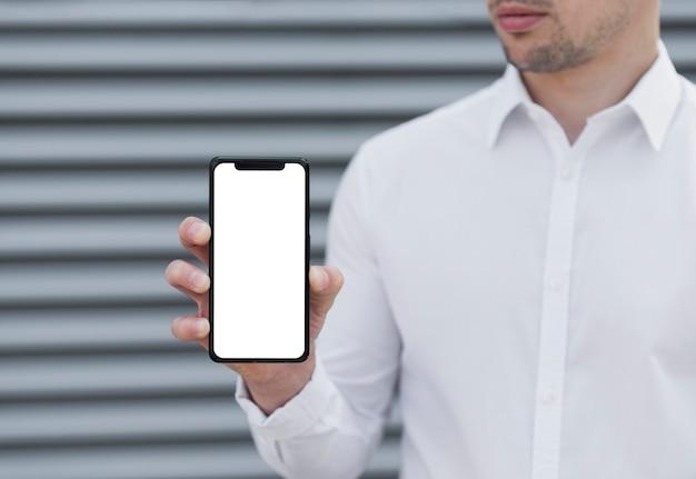 Mann, der iphone modell hält