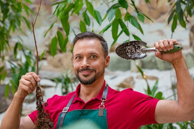 Mann, der jungen baum hält und sich darauf vorbereitet, in erde zu pflanzen.