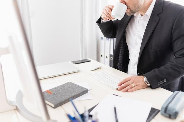 Mann, der kaffee an seinem job trinkt