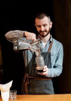 Mann, der kaffee für kunden zubereitet