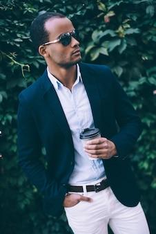 Mann, der kaffee genießt. hübscher junger afrikanischer mann mit sonnenbrille, der kaffeetasse hält und wegschaut, während er im freien vor grünem pflanzenhintergrund steht