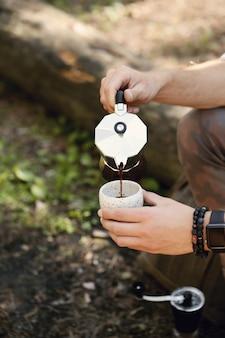 Mann, der kaffee im wald trinkt