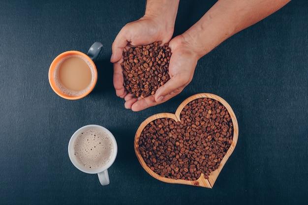 Mann, der kaffee mit kaffeebohnen in einer herzförmigen schüssel auf schwarz hält