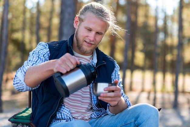 Mann, der kaffee von der thermoskanne gießt
