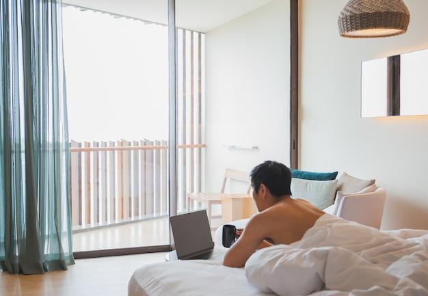 Mann, der kaffee während der arbeit am laptop im bett liegt trinkt