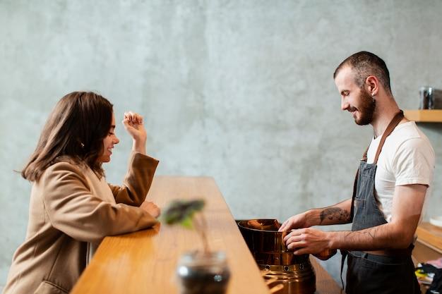 Mann, der kaffee zum kunden zubereitet