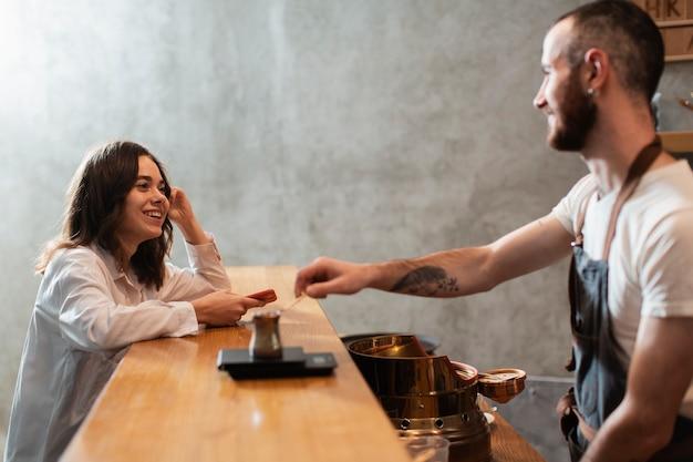 Mann, der kaffeetopf auf bar mit kunden setzt