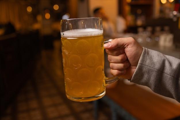 Mann, der kaltes bierglas mit seiner hand hält erfrischung kaltes lagerbier.