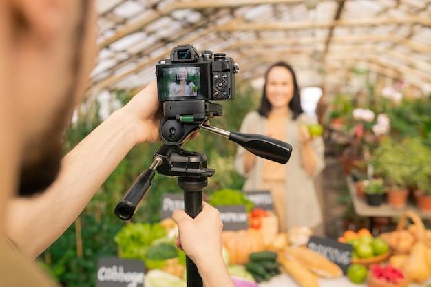 Mann, der kamera auf stativ einstellt, während video über gartenarbeit mit asiatischem landwirt im gewächshaus macht