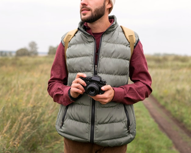 Mann, der kamera in der natur hält