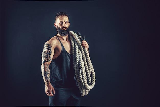 Mann, der kampfseil und fitnessball hält