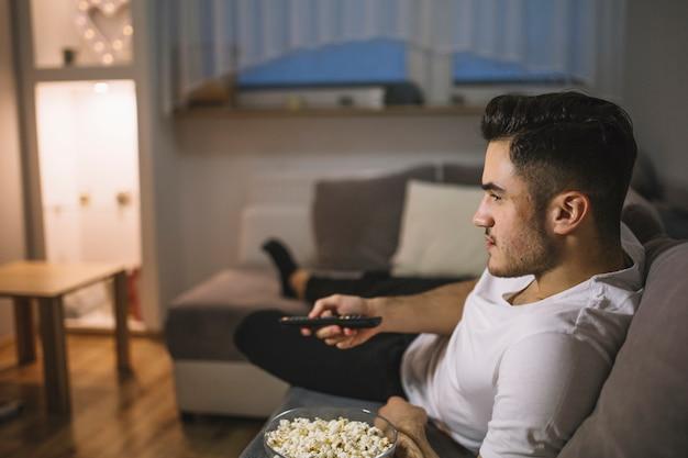 Mann, der kanäle auf fernsehapparat schaltet