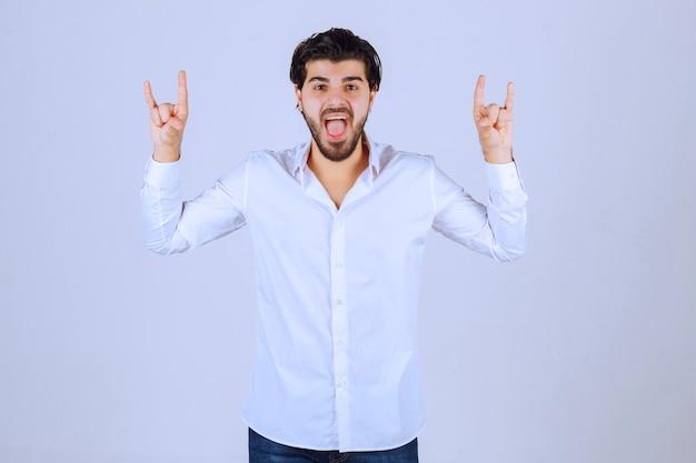 Mann, der kaninchen- oder wolfshandzeichen zeigt.