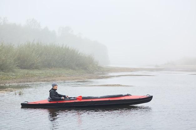 Mann, der kanu am kalten tag im see paddelt, sich auf aktive weise ausruht, im boot sitzt und die schöne natur betrachtet, jacke und mütze trägt, wassersport