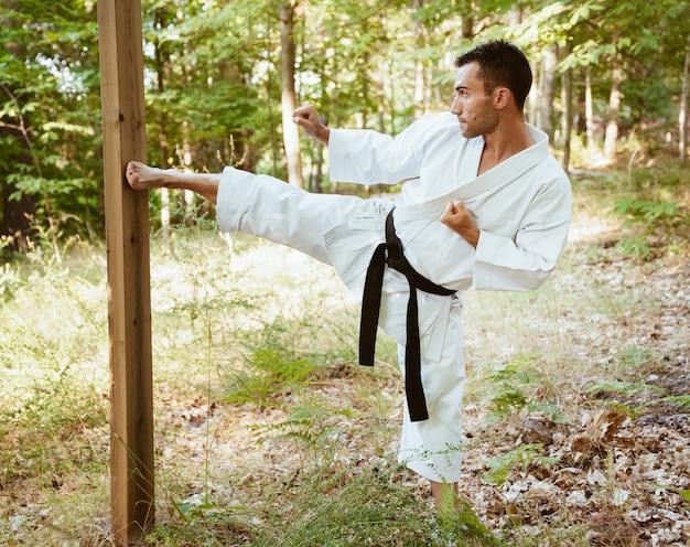 Mann, der karate in der natur praktiziert