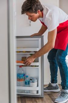 Mann, der karotte im kühlschrank hält