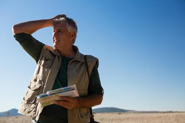 Mann, der karte auf landschaft hält