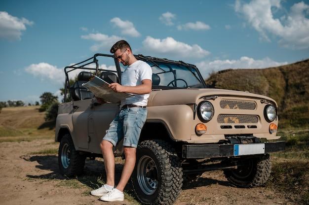 Mann, der karte beim reisen mit dem auto hält