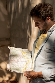 Mann, der karte im schatten betrachtet