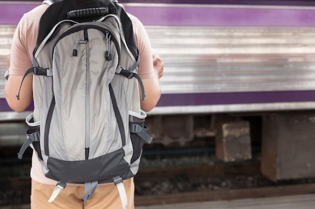 Mann, der karte mit rucksack am bahnhof hält