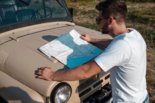 Mann, der karte überprüft, während er alleine mit dem auto reist