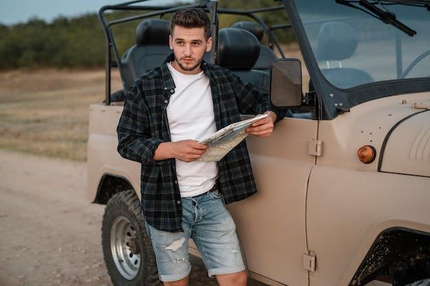 Mann, der karte überprüft, während er mit dem auto allein reist