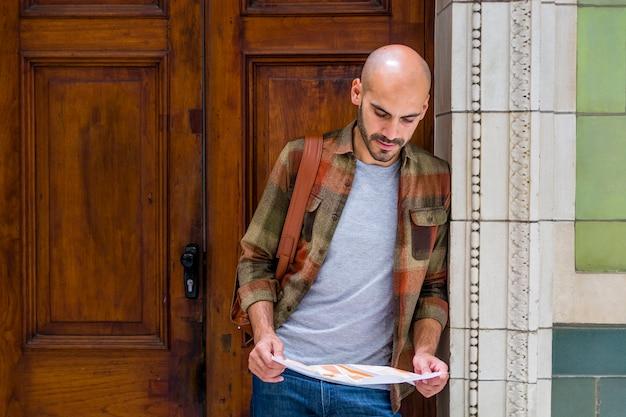 Mann, der karte verwendet, um sich in der stadt zu orientieren
