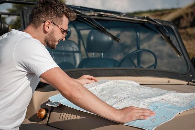 Mann, der karte während der fahrt mit dem auto überprüft