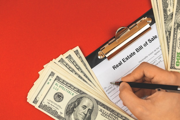Mann, der kaufvertrag immobilienvertrag ausfüllt. unterzeichnung des vertragskonzeptes. bürotisch mit geld