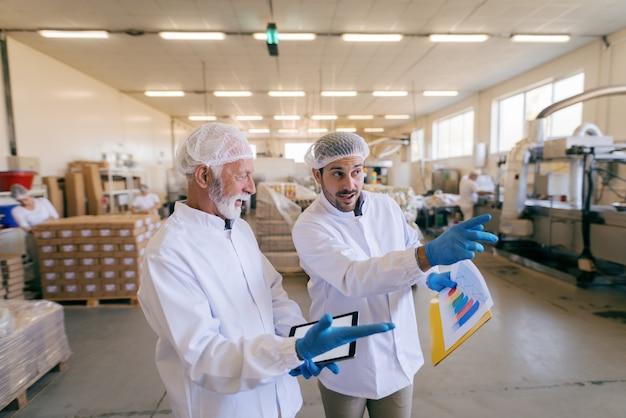 Mann, der kisten stapelt, während anderer mann steht und tablette verwendet. innenausstattung der lebensmittelfabrik.