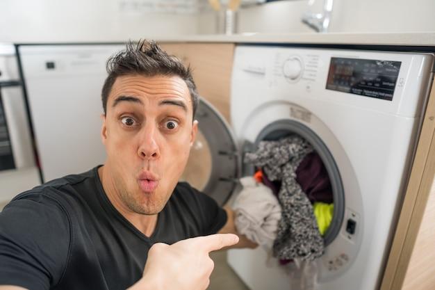 Mann, der kleidung in die waschmaschine steckt, in der küche, besorgt, weil er viel kleidung waschen muss. nahaufnahme.
