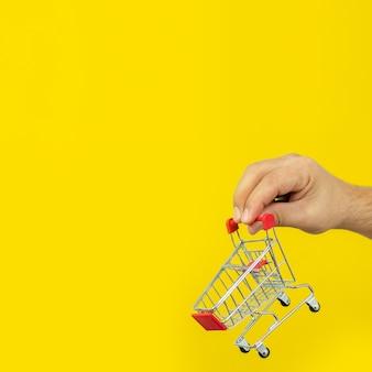 Mann, der kleinen einkaufswagenwagen über gelbem hintergrund hält. online-shopping und schnelles lieferkonzept