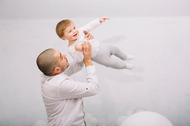 Mann, der kleines baby auf händen erhebt
