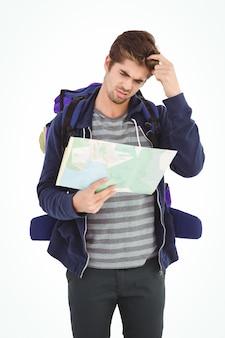 Mann, der kopf beim schauen in der karte verkratzt